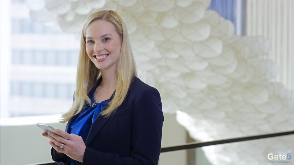 woman working in office smiling at camera with an ipad for promotional video