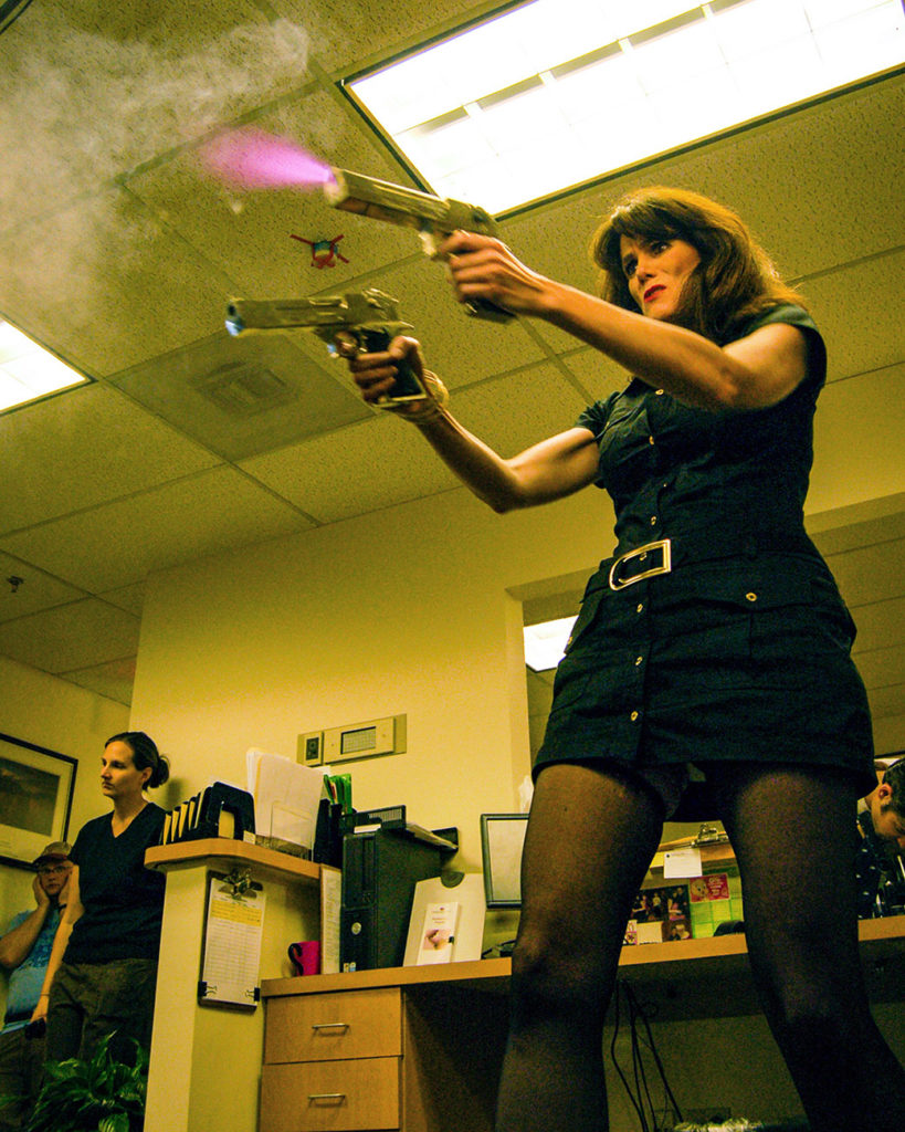 woman firing guns in office in behind the scenes film set photo