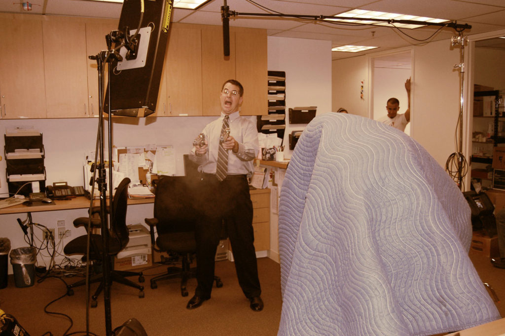 a man fires guns at his coworkers in behind the scenes film set photo