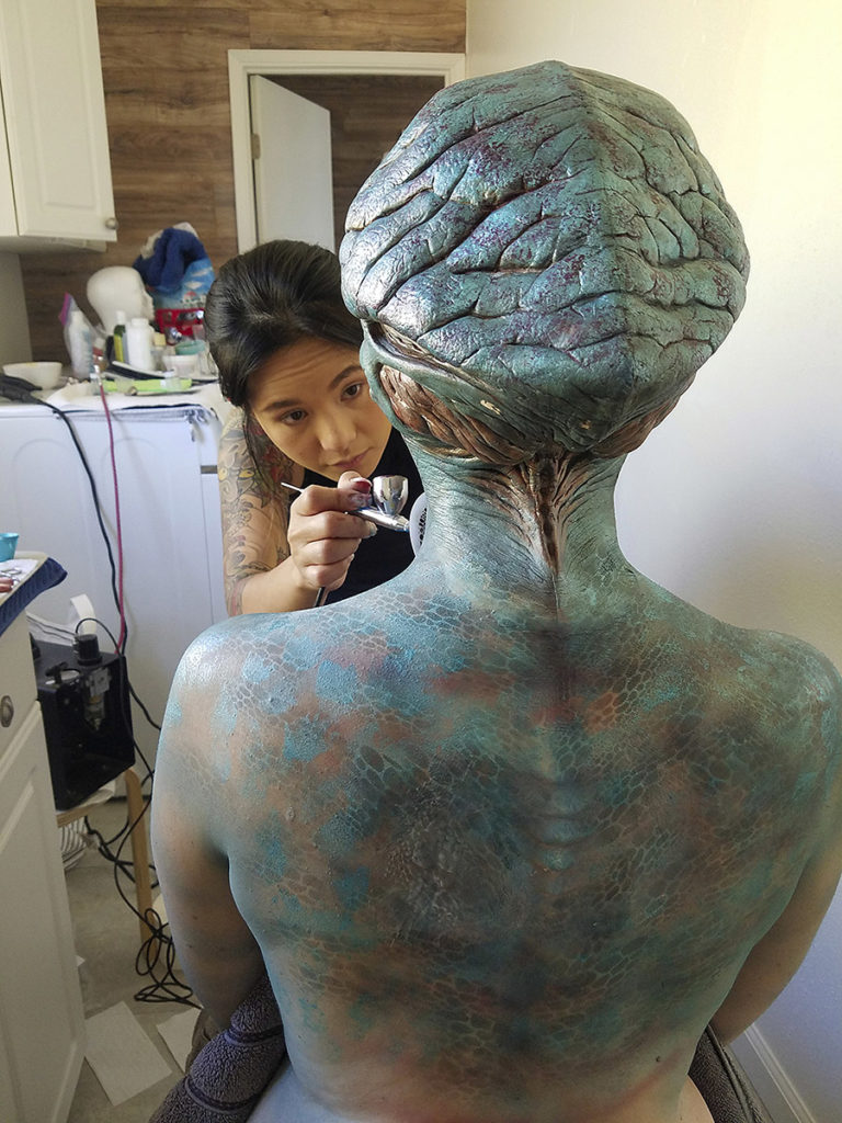 makeup artist applying body paint and alien prosthetics on actor