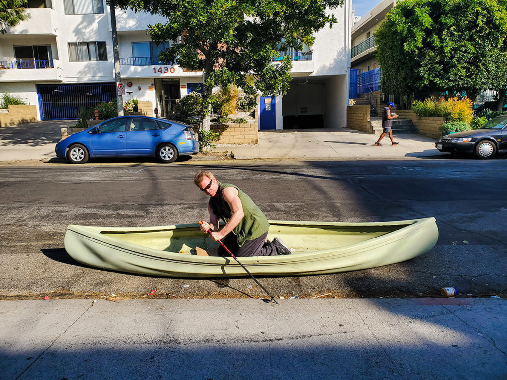a man rows a canoe in a city street