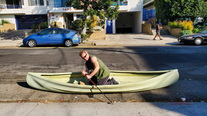 a man rows a canoe in a city street