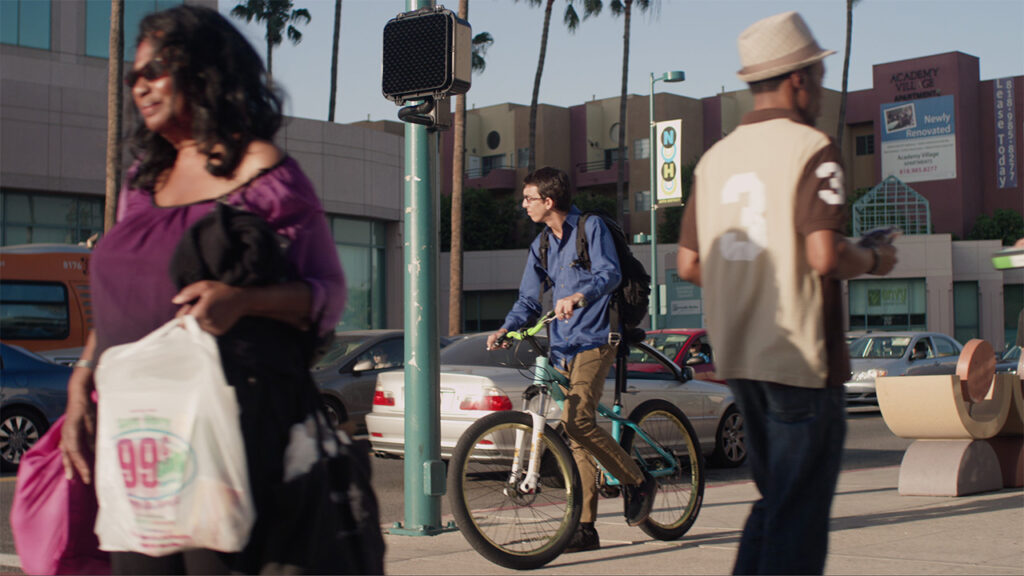 a man on a bike and two other people look frozen in time at a city street intersection while they wait for the light to change